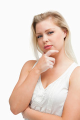 Thoughtful blonde woman placing her hand on her chin