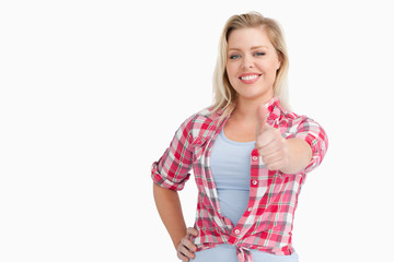 Happy blonde woman placing her thumbs up