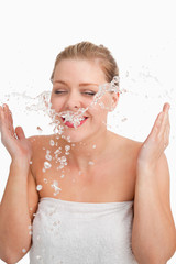 Happy blonde woman splashing her face