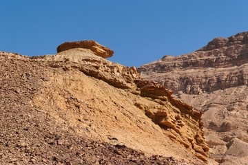 Weathered orange rock on top of dune in desert canyon