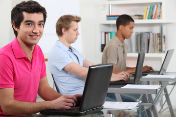 Young men working on their assignments in a computer lab