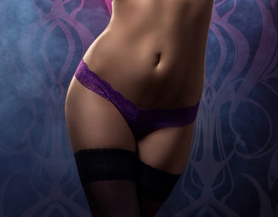 Sexy belly of a young woman in erotic violet panties