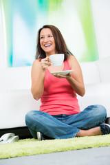 fröhliche junge frau trinkt einen milchkaffee
