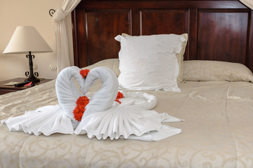 decorative two nice towels swans on  bed sheet