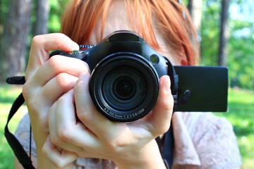 Girl holding a camera while taking outdoors pictures