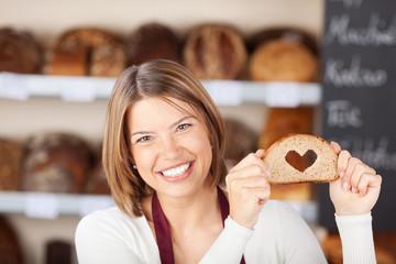 verkäuferin mit herz-brot in der bäckerei