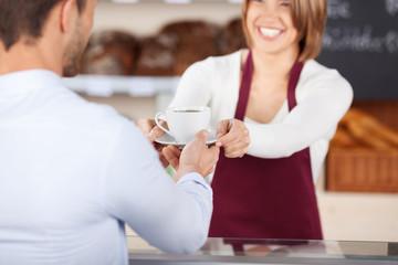 kunde bekommt eine tasse kaffee in der bäckerei