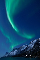 Fototapete - Aurora Borealis above mountains in Norway