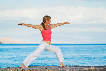 Beautiful Yoga woman Practicing Yoga by the Ocean