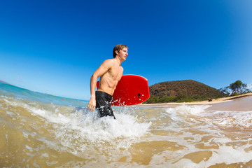 Wall Mural - Young Man with Boogie Board at the Beach
