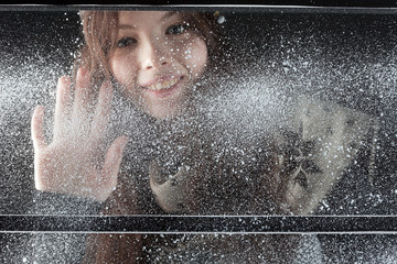young happy girl behind snow window