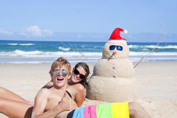 Wall Mural - Couple having fun at beach with sandman