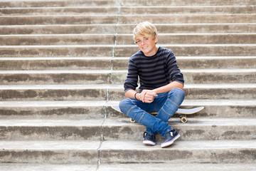 handsome teen boy sitting on skateboard