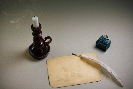 Candle in vintage candlestick, quill and  inkwell, old paper