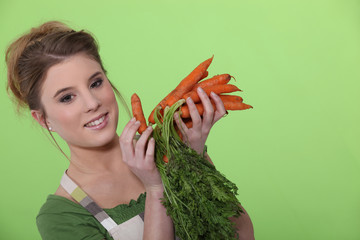 Attractive woman holding carrots