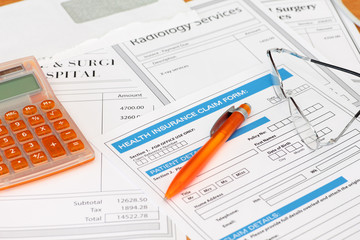 Surgery bills with health insurance claim calculator and pen
