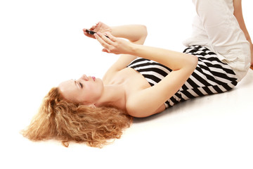Relaxed woman using her cellphone isolated. Top view