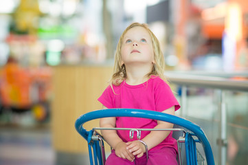 Adorble baby sit on shopping cart in mall