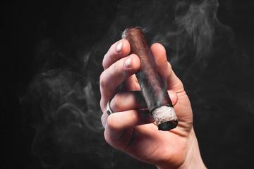 Closeup photo of man hand holding big brown smoking cigar