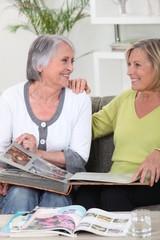 senior women looking photo album