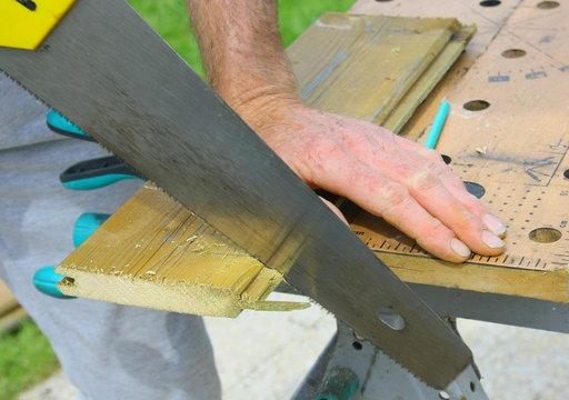 homme sciant une planche de bois