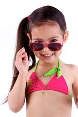 jolie petite fille avec maillot de bain et lunette de soleil