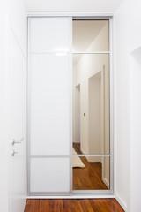Modern white wardrobe with sliding glass door