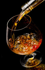 Fototapete - The glass with splashes cognac on black background