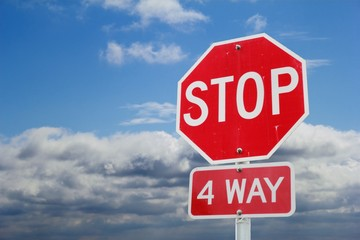 4 Way Stop sign in front of clouds