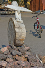 wooden fliing figure like an angel on the rock with a bicycle ag