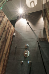 modern shower faucet with dark tiled wall and printed wood