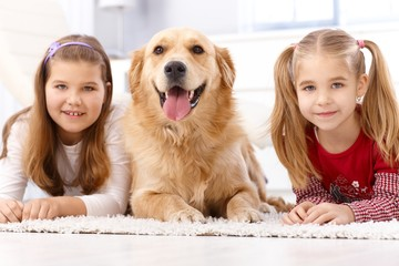 Little girls and dog lying on floor smiling