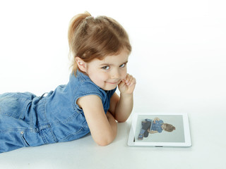 Little girl is watching concentrated photographs on touchpad