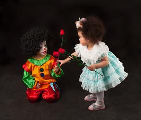 little girl giving flowers small clown