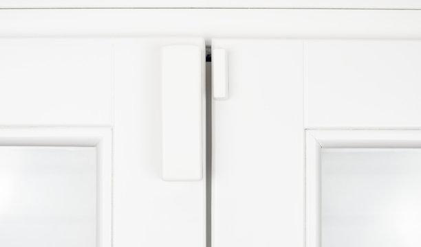 Wireless alarm sensor for window and door on white wooden sash