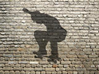 ombre de skate-boarder sur mur de briques