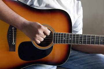 closeup view of right hand strumming an acoustic guitar