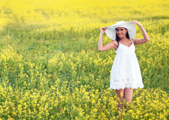 Smiling pretty girl in white in blooming field