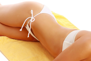 A part of a female body in a white swimsuit lying