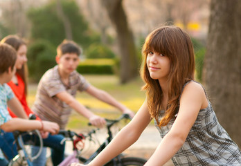 Beautiful teenage girl with her friends riding bicycles