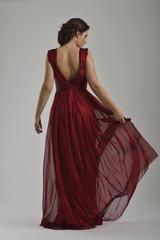 elegant woman in fashionable dress posing in the studio