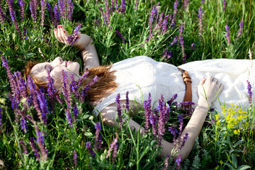 Young fashion girl lying down at green grass.
