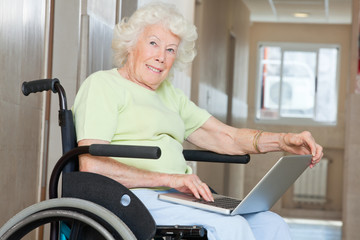 Senior Woman In Wheelchair Using Laptop