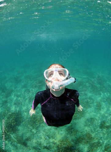 Wall mural Woman snorkeling underwater in ocean