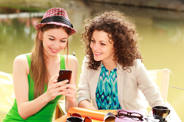 Two beautiful women playing on a smart-phone and chatting