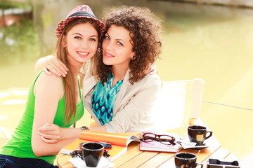 Two beautiful women drinking coffee and smiling