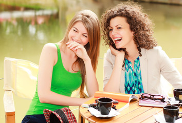 Two beautiful women laughing over a cofee