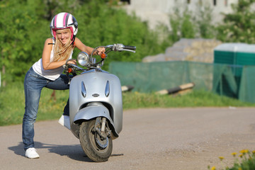 portrait of young happy woman on motorbike / scooter outdoors