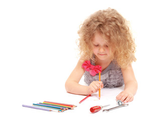 A happy little girl drawing with pencils, isolated on white