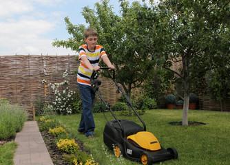 Teen boy mows the lawn mower electric